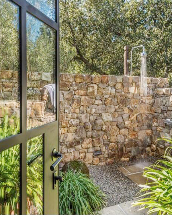 exterior stacked stone surrounding the outdoor shower